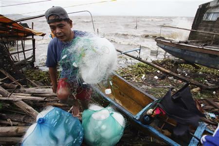 A fisherman carries his net after making it safely back to shore in the fishing village after a strong winds from Typhoon Haiyan battered Bayog town in Los Banos, Laguna city, south of Manila November 8, 2013. REUTERS/Charlie Saceda