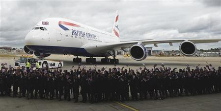 Workers welcome British Airways' new Airbus A380 as it taxis to a hanger after landing at Heathrow airport in London July 4, 2013. REUTERS/Paul Hackett