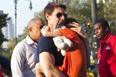 Actor Tom Cruise carries his daughter Suri into the Chelsea Piers sports facility in New York, July 17, 2012. REUTERS/Andrew Burton