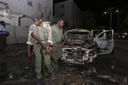 Somali policemen inspect the scene of an explosion outside the Maka Al-Mukarama hotel in Somalia's capital Mogadishu, November 8, 2013. REUTERS/Feisal Omar (