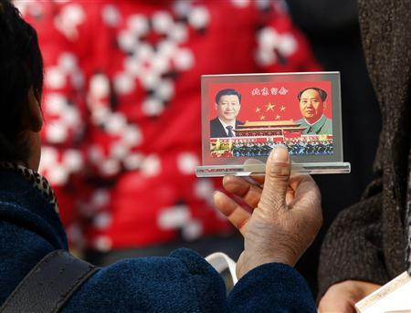 A street vendor displays a souvenir with pictures of Chinese President Xi Jinping (L) and the late Chinese Chairman Mao Zedong to visitors at the Tiananmen Square in Beijing November 8, 2013. REUTERS/Kim Kyung-Hoon
