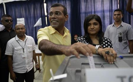 Maldivian Democratic Party (MDP) presidential candidate Mohamed Nasheed, who was ousted as president in 2012 (C), casts his vote at a polling station during the presidential elections in Male November 9, 2013. REUTERS/Waheed Mohamed