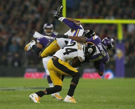 Minnesota Vikings wide receiver Jerome Simpson (R) is brought down by Pittsburgh Steelers cornerback Ike Taylor and another defender in the second quarter during their NFL football game at Wembley Stadium in London, September 29, 2013. REUTERS/Suzanne Plunkett