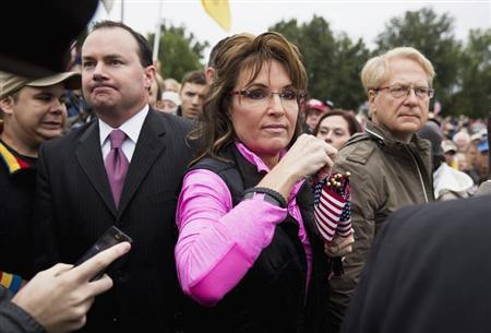 Senator Mike Lee (L)(R-UT) watches as Former Alaska Governor Sarah Palin hands out American Flags to protesters during the ''Million Vet March on the Memorials'' at the U.S. National World War II Memorial in Washington October 13, 2013. REUTERS/Joshua Roberts