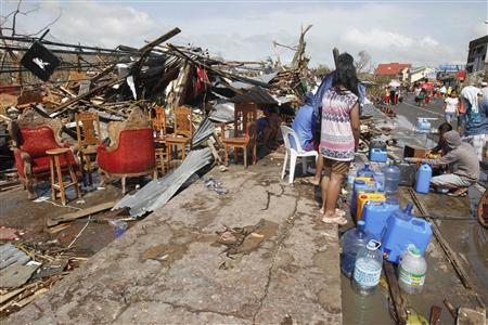 Survivors queue to get water from a faucet near damaged houses after super Typhoon Haiyan battered Tacloban city, central Philippines November 10, 2013. REUTERS/Romeo Ranoco