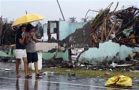Women share an umbrella as they look at the remains of a house which was destroyed after Super Typhoon Haiyan battered Tacloban city in central Philippines November 10, 2013. REUTERS/Erik De Castro