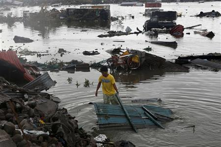 A man retrieves a house roofing from a river after Super Typhoon Haiyan battered Tacloban city in central Philippines November 10, 2013. REUTERS/Erik De Castro