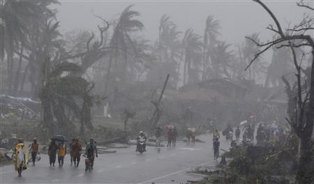 Survivors walk on a road amidst heavy downpour after Typhoon Haiyan battered Tacloban city in central Philippines November 10, 2013. REUTERS/Erik De Castro