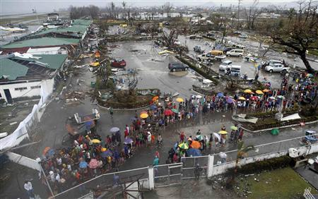 Typhoon victims queue for food and water outside an airport after Super Typhoon Haiyan battered Tacloban city in central Philippines November 10, 2013. REUTERS/Erik De Castro