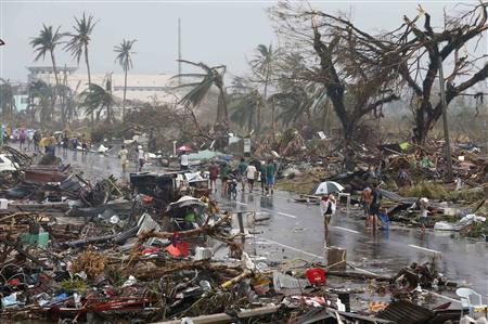 Residents walk on a road littered with debris after Super Typhoon Haiyan battered Tacloban city in central Philippines November 10, 2013. REUTERS/Erik De Castro