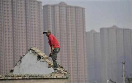 A man stands on the top of a building as farmers' houses are demolished to make space for new property to be built, in front of a residential compound in Hefei, Anhui province, October 19, 2013. REUTERS/Stringer