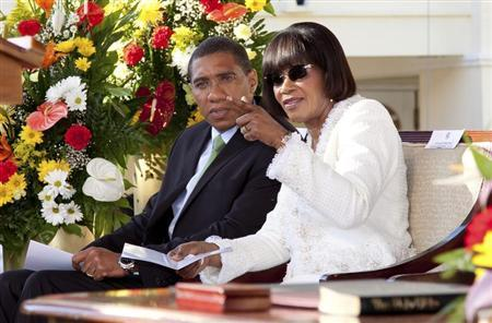 Incoming Jamaican Prime Minister Portia Simpson Miller (R) speaks with outgoing Prime Minister Andrew Holness during her swearing-in ceremony at King's House in Kingston January 5, 2012. REUTERS/Gilbert Bellamy