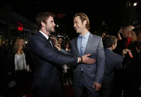 Cast member Chris Hemsworth (R) greets his brother actor Liam Hemsworth at the premiere of ''Thor: The Dark World'' at El Capitan theatre in Hollywood, California November 4, 2013. The movie opens in the U.S. on November 8. REUTERS/Mario Anzuoni