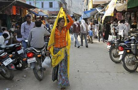 A village woman walks through a street at Kasba Bonli town in Rajasthan October 30, 2013. REUTERS/Shyamantha Asokan/Files