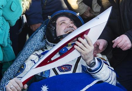 International Space Station (ISS) crew member Russian cosmonaut Fyodor Yurchikhin holds the torch of the 2014 Sochi Winter Olympic Games after landing near the town of Zhezkazgan in central Kazakhstan November 11, 2013. REUTERS/Shamil Zhumatov