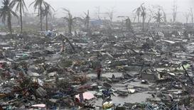 """Люди среди обломков зданий, разрушенных тайфуном """"Хайян"""", 10 ноября 2013 года. Один из самых сильных тайфунов в истории, обрушившийся на Филиппины в конце прошлой недели, мог унести жизни 10.000 человек, сообщил высокопоставленный представитель полиции. REUTERS/Erik De Castro"""