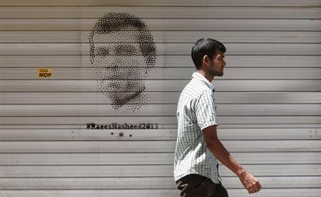 A Maldivian man walks past an image of Maldivian presidential candidate Mohamed Nasheed ahead of their presidential election in Male, November 7, 2013. REUTERS/Stringer