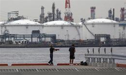 Мужчины рыбачат у НПЗ в Кавасаки 5 июля 2012 года. Цены на нефть растут, так как Иран не смог договориться со странами Запада по поводу своей ядерной программы, а расчетное потребление топлива в Китае повысилось. REUTERS/Toru Hanai