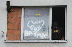 Золтан Кохари, известный как Словацкий Бэтмен, выглядывает из окна своей квартиры в городе Дунайска-Стреда 9 марта 2012 года. Мужчина из Сингапура с необычным именем супергероя оказался злодеем, который употребляет наркотики и крадет у родного брата. REUTERS/Radovan Stoklasa