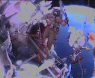 Russian astronaut Oleg Kotov holds an Olympic torch as he begins a spacewalk outside the International Space Station in this still image taken from video courtesy of NASA TV, November 9, 2013. REUTERS/NASA TV/Handout via Reuters