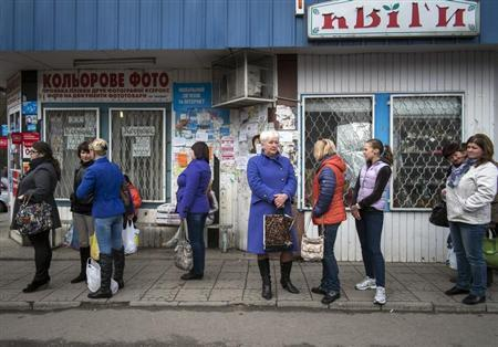 People wait for a bus at a bus station in the small Ukrainian town Pustomyty, near the western city Lviv October 31, 2013. REUTERS/Gleb Garanich