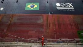 Un trabajador pasa frente al barco productor FPSO OSX-1 de OSX en Río de Janeiro, nov 17 2011. Los negocios con las acciones de OSX Brasil fueron suspendidas el lunes hasta que se confirme el inicio del proceso judicial de su solicitud de protección por quiebra, informó la bolsa de Sao Paulo. REUTERS/Sergio Moraes