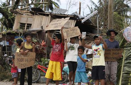 Children hold signs asking for help and food along the highway, after Typhoon Haiyan hit Tabogon town in Cebu Province, central Philippines November 11, 2013. REUTERS/Charlie Saceda