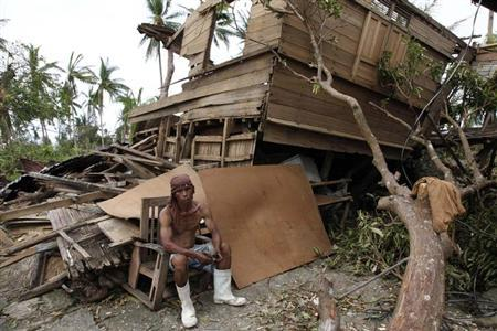 A man takes a break from salvaging reusable woods from his damaged house after super Typhoon Haiyan hit Tabogon town in Cebu Province, central Philippines November 11, 2013. REUTERS/Charlie Saceda