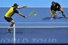 Bob Bryan of the U.S. slips as his brother Mike Bryan plays a shot during their men's doubles final tennis match against David Marrero of Spain and Fernando Verdasco of Chile at the ATP World Tour Finals at the O2 Arena in London November 11, 2013. REUTERS/Toby Melville