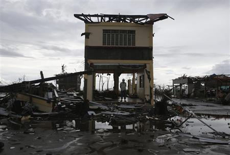 A man stands on the ground floor of his damaged house after super typhoon Haiyan battered Palo, Leyte province in central Philippines November 12, 2013. REUTERS/Erik De Castro