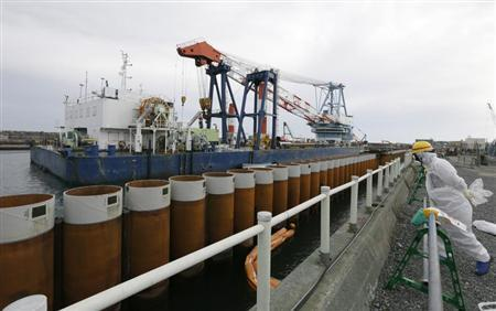 A Tokyo Electric Power Co. (TEPCO) employee wearing a protective suit and mask stands next to an impervious wall made of a steel pipe sheet pile installed along the coast, facing nuclear reactor buildings No. 1 to No. 4, at the tsunami-crippled TEPCO's Fukushima Daiichi nuclear power plant in Fukushima prefecture, November 7, 2013. REUTERS/Kimimasa Mayama/Pool
