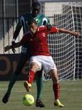 Jogador da equipe egípcia Al-Ahli Ahmed Abd El-Zaher disputa a bola em partida contra o Coton Sport, de Camarões, válida pela Liga dos Campeões da África, no estádio El-Gouna, em Hurghada, no Egito. Após marcar um gol, Zaher fez o gesto com quatro dedos que representa a resistência da Irmandade Muçulmana diante da repressão das forças de segurança ao grupo de Mursi. 20/10/2013. REUTERS/Amr Abdallah Dalsh