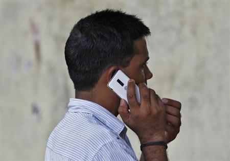 A man speaks on a mobile phone at a marketplace in New Delhi June 18, 2013. REUTERS/Anindito Mukherjee/Files