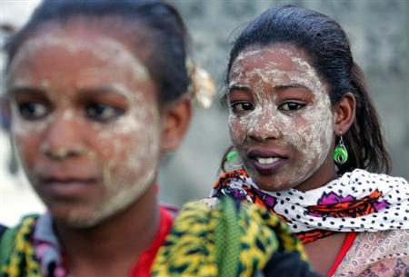 Comoran women with faces smeared yellow by the herbal lotion popular in the islands attend a welcoming ceremony for Said Larifou in Foumboni village, Comoros Islands April 21, 2005. REUTERS/Radu Sigheti/Files