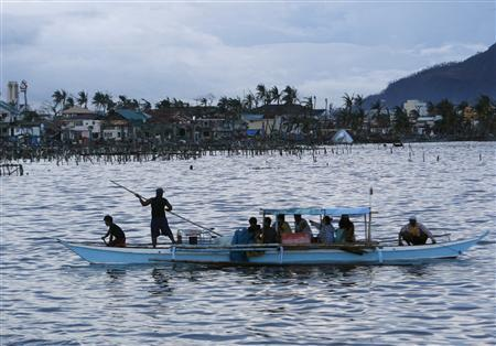 People leave on a boat against the backdrop of a destroyed fishing community after the Super typhoon Haiyan battered Tacloban city in central Philippines November 12, 2013. REUTERS/Edgar Su