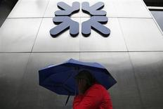 A woman shelters under an umbrella as she walks past a branch of the Royal Bank of Scotland in the City of London September 17, 2013. REUTERS/Stefan Wermuth