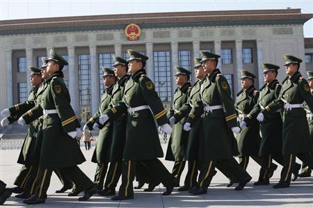 Paramilitary soldiers march as they patrol around the Tiananmen square and the Great Hall of the People where the Chinese Communist Party plenum is being held, is seen in the background in Beijing, November 12, 2013. REUTERS/Kim Kyung-Hoon