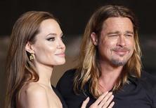 HA atriz Angelina Jolie e o ator Brad Pitt posam para fãs em Tóquio, em 29 de julho de 2013. Uma dublê de Angelina Jolie teve o telefone celular grampeado por um detetive que buscava informações sobre o relacionamento da atriz com Brad Pitt para repassar a um tabloide britânico do magnata Rupert Murdoch, segundo informações apresentadas nesta terça-feira no julgamento de dois ex-editores de jornal. REUTERS/Issei Kato (JAPAN - Tags: ENTERTAINMENT) - RTX123LR