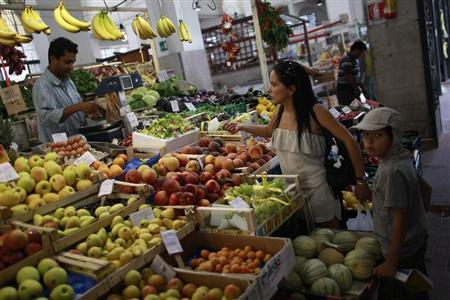 A woman buys fruit in a market in downtown Rome August 5, 2011. REUTERS/Tony Gentile
