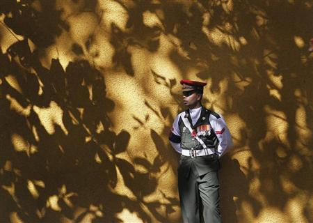 A soldier on duty looks on as he stands guard at an entrance at the World World II war memorial during an event marking Remembrance Day, also known as Poppy day, to commemorate the sacrifices of members of the armed forces and of civilians in times of war, in Colombo November 10, 2013. REUTERS/Dinuka Liyanawatte