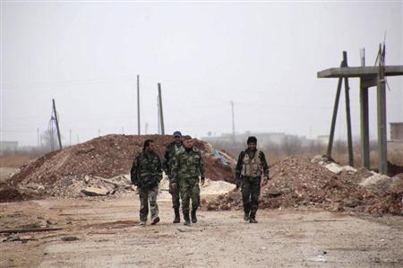 Forces loyal to Syria's President Bashar al-Assad carry their weapons as they walk along a road in the town of Tel Arn in Aleppo after capturing it from rebels November 12, 2013. REUTERS/George Ourfalian