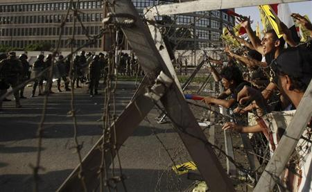 Members of the Muslim Brotherhood and supporters of ousted Egyptian President Mohamed Mursi shout slogans next to barbed wire as army soldiers and the riot police look on, during a protest against the military, at Cairo's Nasr City district, October 4, 2013. REUTERS/Amr Abdallah Dalsh