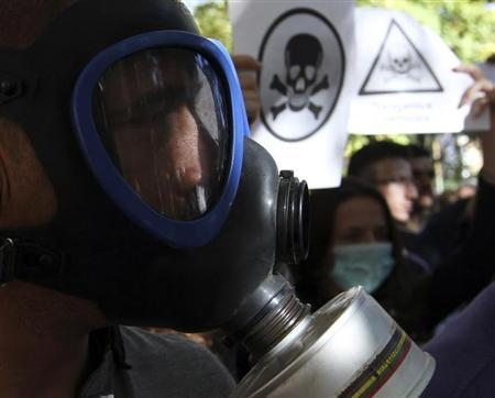 A demonstrator wears a gasmask during a protest against the dismantling of Syrian chemical weapons in Albania in front of the Prime Minister's office in Tirana November 7, 2013. REUTERS/Arben Celi