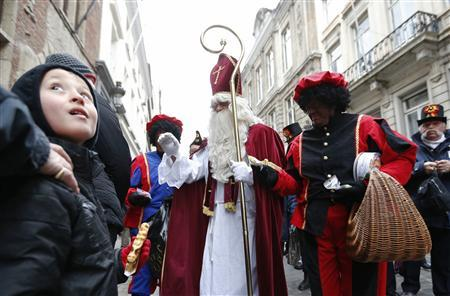 Saint Nicholas (C) is escorted by his assistants called 'Zwarte Piet' (Black Pete) during a traditional parade in central Brussels in this December 1, 2012 file photo. REUTERS/Francois Lenoir/Files