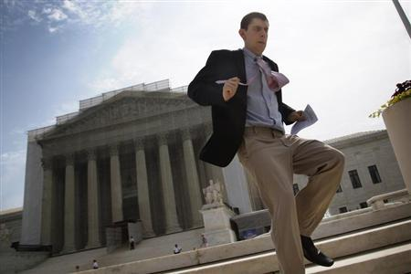 A television news producer sprints down the steps from the U.S. Supreme Court building with their printed rulings in cases heard earlier this year in Washington, June 24, 2013. REUTERS/Jonathan Ernst