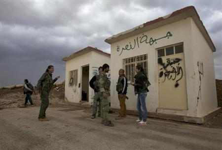 Members of the Kurdish People's Protection Units (YPG) chat together as they stand in front of a base, that used to be for Islamist Syrian rebel group Jabhat al-Nusra, after capturing it from them in Al-Rmelan, Qamshli province November 11, 2013. REUTERS/Stringer