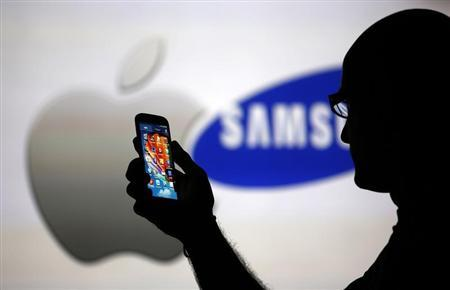 A man is silhouetted against a video screen with Apple and Samsung logos as he poses with a Samsung Galaxy S4 in this photo illustration taken in the central Bosnian town of Zenica, August 14, 2013. REUTERS/Dado Ruvic