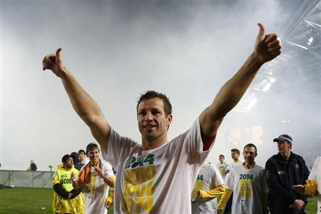 Australia's captain Lucas Neill celebrates after defeating Iraq to qualify for the 2014 FIFA World Cup, at Australia Stadium in Sydney June 18, 2013 file photo. REUTERS/Daniel Munoz