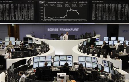 Traders are pictured at their desks in front of the DAX board at the Frankfurt stock exchange November 7, 2013. REUTERS/Remote/Stringer