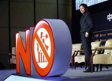 Sohu CEO Charles Zhang stands next to an installation symbolizing action against copyright violation during a joint news conference in Beijing, November 13, 2013. A group including Chinese Internet firms Tencent Holdings and Sohu.Com Inc as well as a top U.S. film industry body said on Wednesday it is seeking 300 million yuan in damages from China's Baidu Inc and others for copyright violation. The Chinese character on the installation reads ''steal''. REUTERS/Kim Kyung-Hoon
